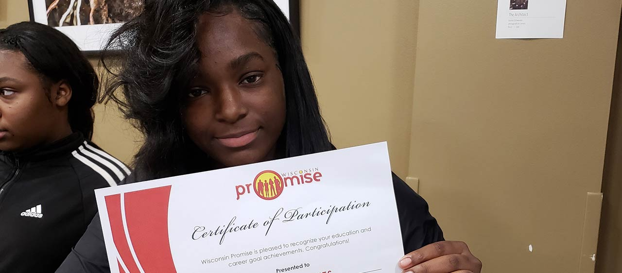 Promise participant holds up diploma and smiles.